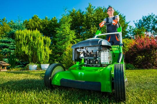 Gardner cutting grass with lawn mower in Torrance, CA